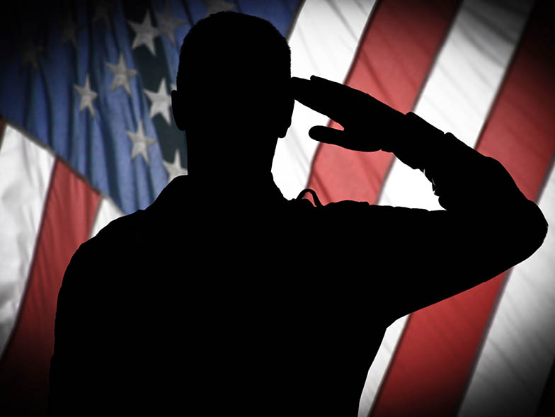 silhouette soldier saluting in front of american flag