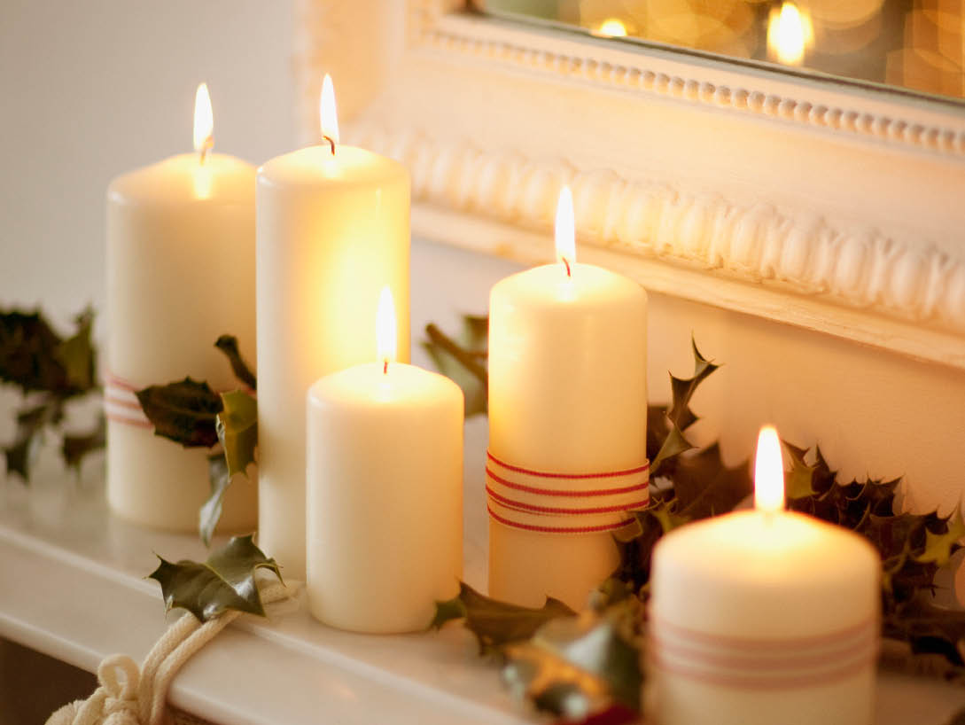 white candles lit on mantel with vines