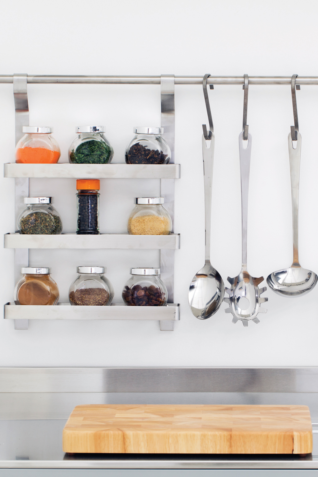 Kitchen utensils and spice rack hanging above sink