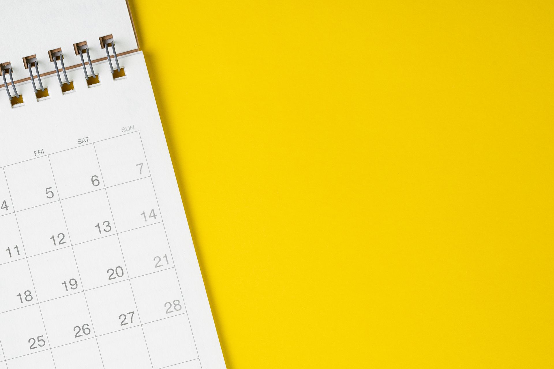 White clean calendar on solid yellow background