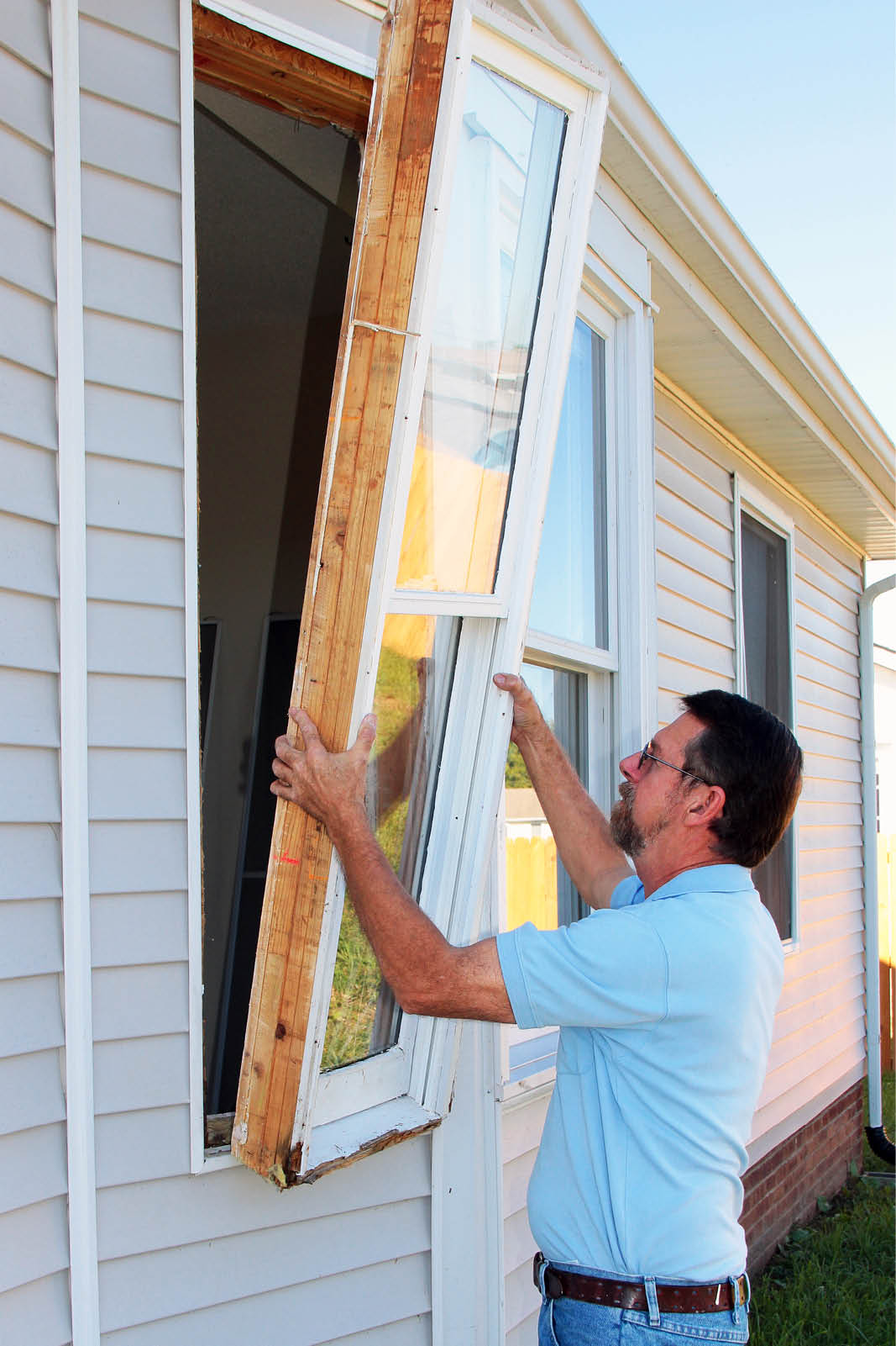 man installing window in home