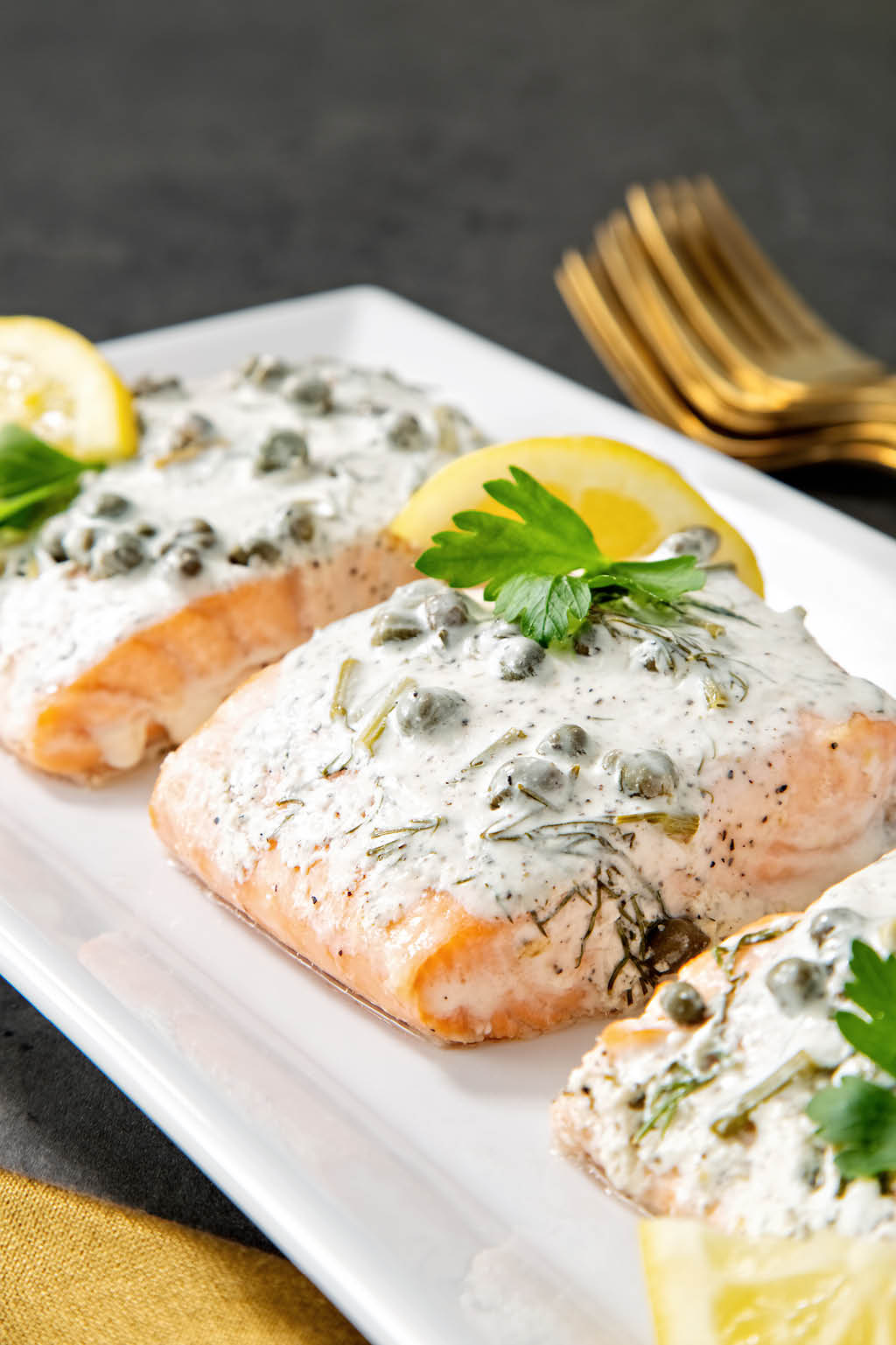 White serving tray of salmon with lemon capers and dill with golden napkin in foreground