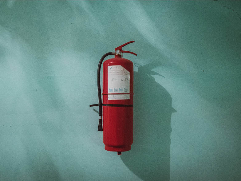 Fire extinguisher against blue wall