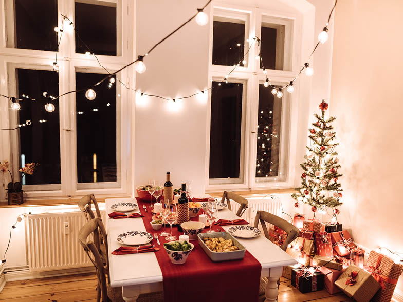 Dining table set up for Christmas party with string lights and tiny Christmas tree