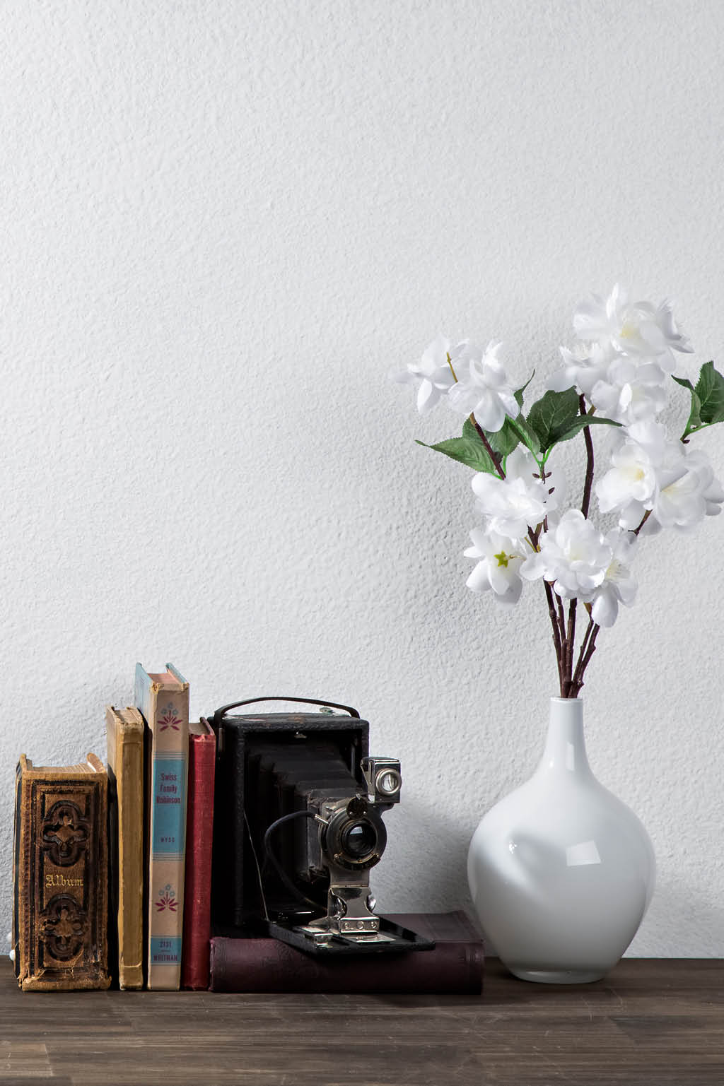 white wall and flowers with books