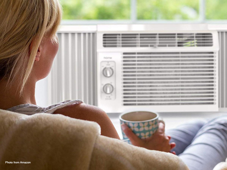 Woman sitting in front of window air conditioning unit