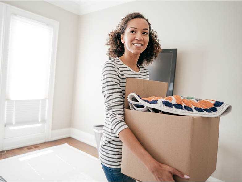 Smiling woman carrying box