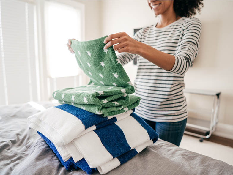 Smiling woman folding towels on bed