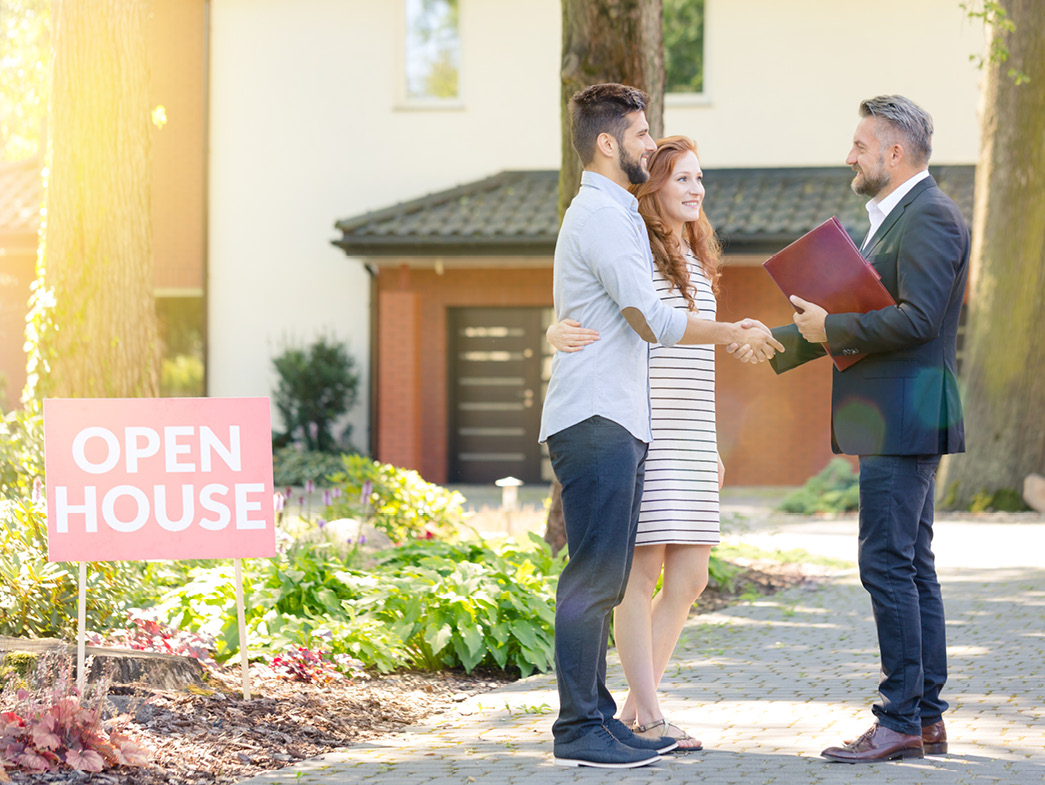 Couple shaking hand with agent outside of home beside