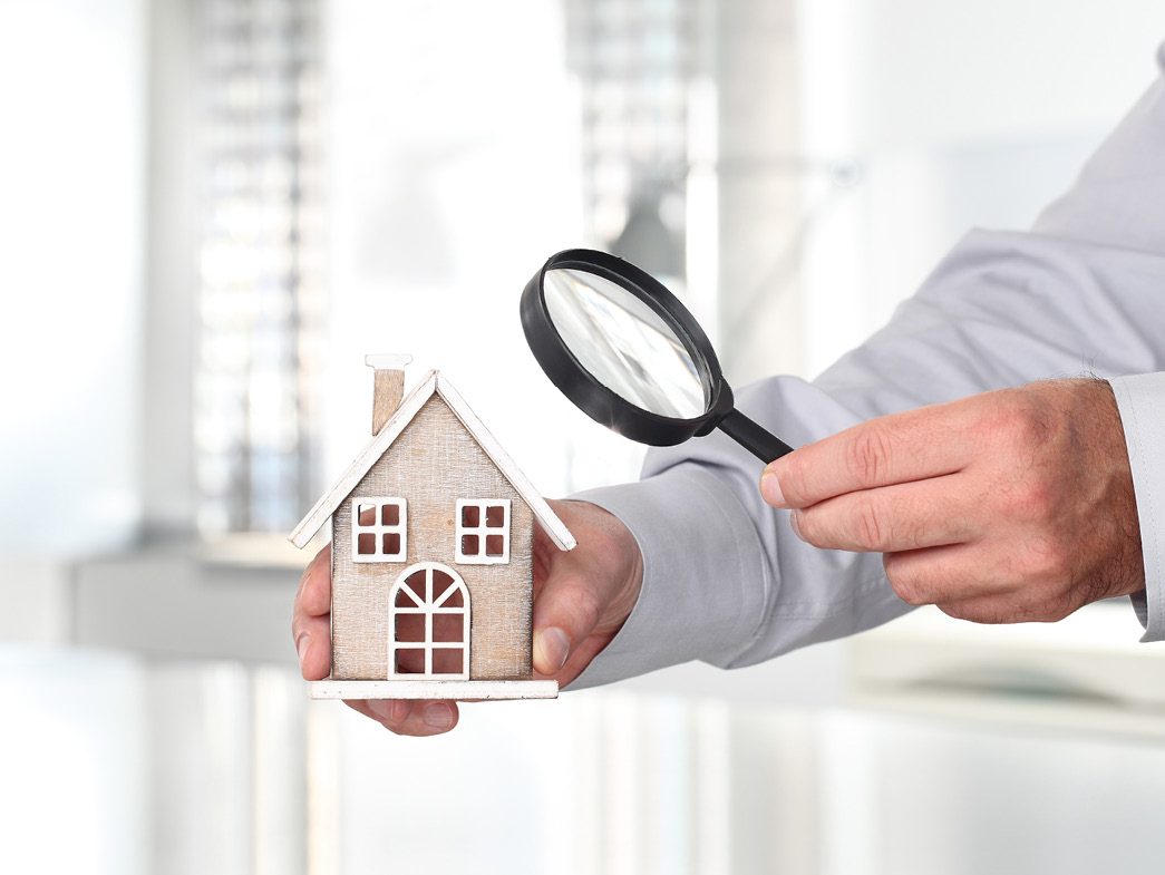 Person holding miniature house in one hand and a magnifying glass in the other
