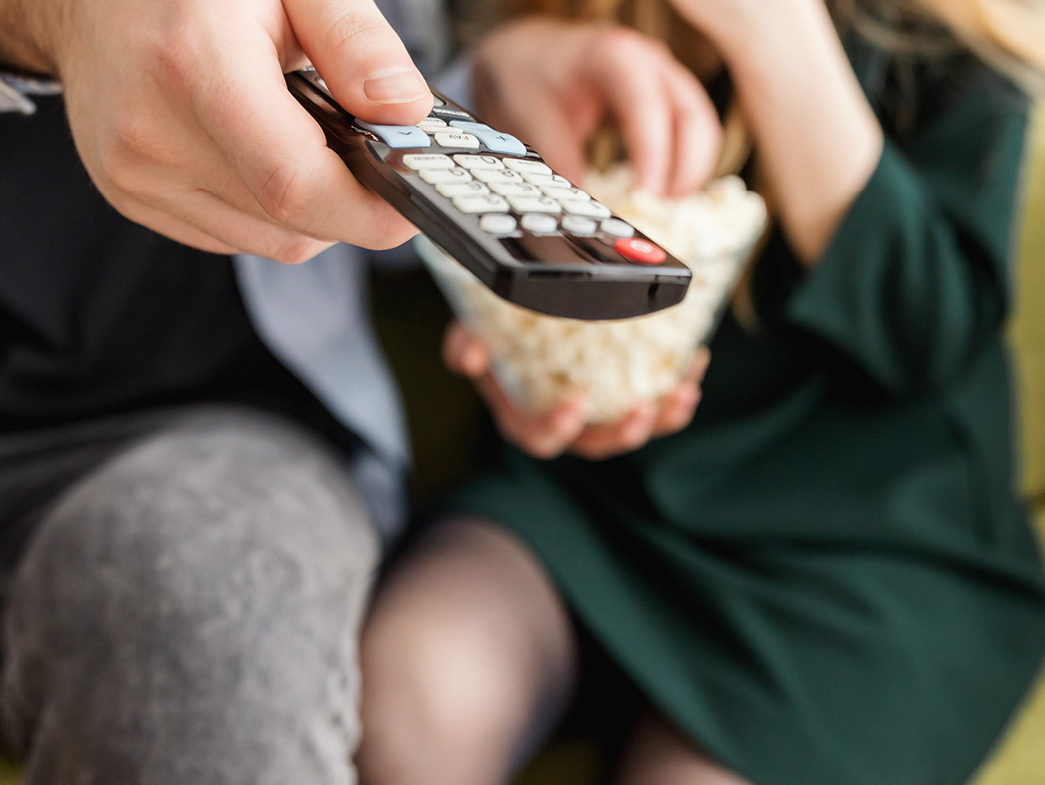Person holding tv remote up with other person holding popcorn in background