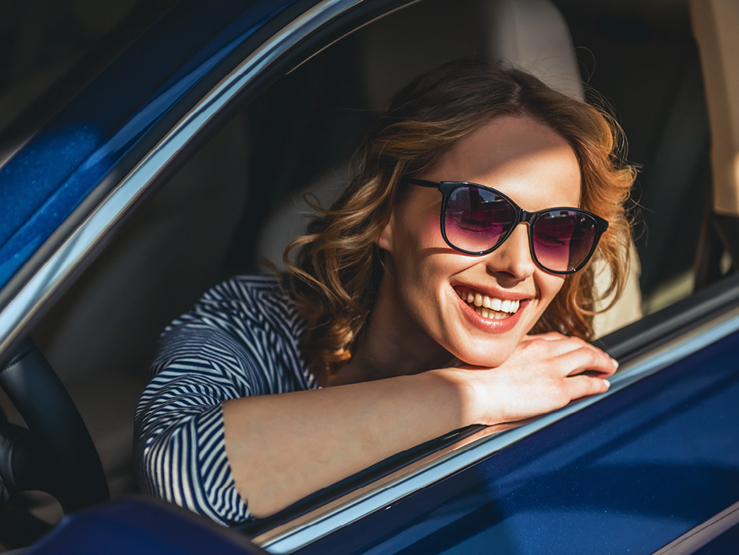 Woman with sunglasses smiling and resting head on car window