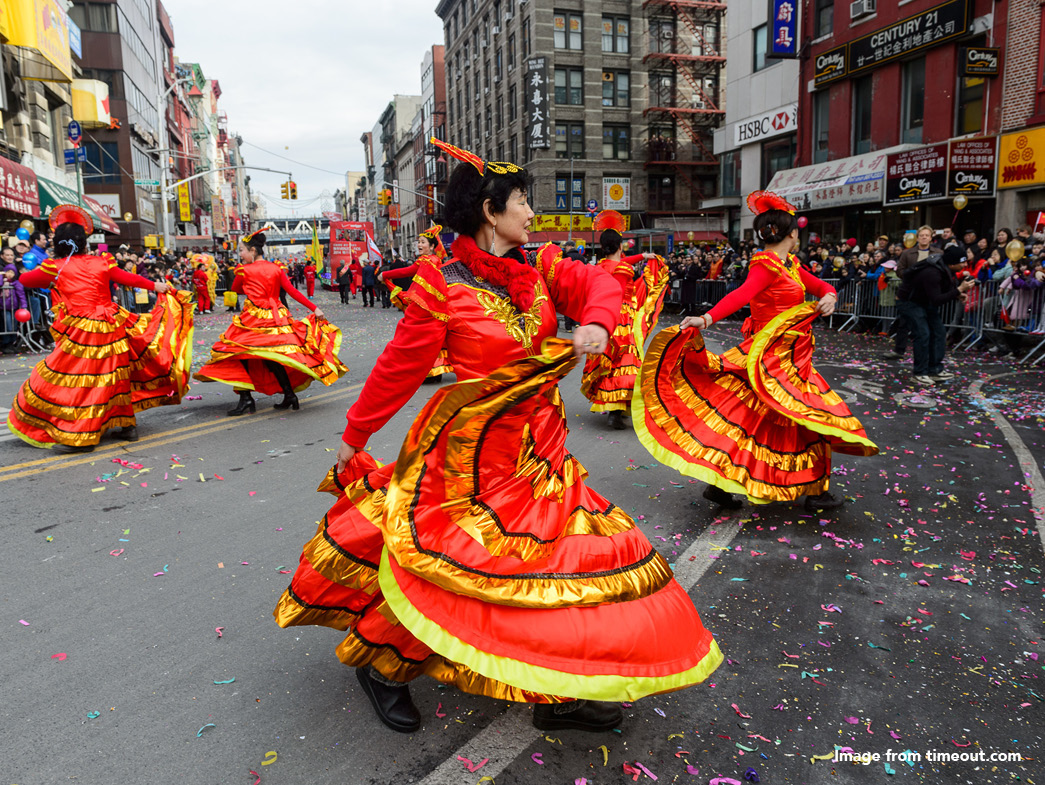 Chinese women dressed in red and gold dresses dancing in the street