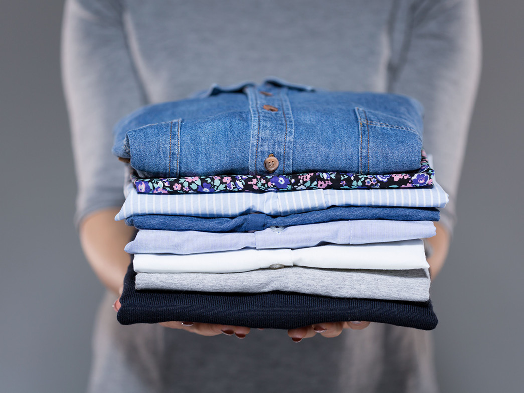Woman holding stack of neatly folded clothes