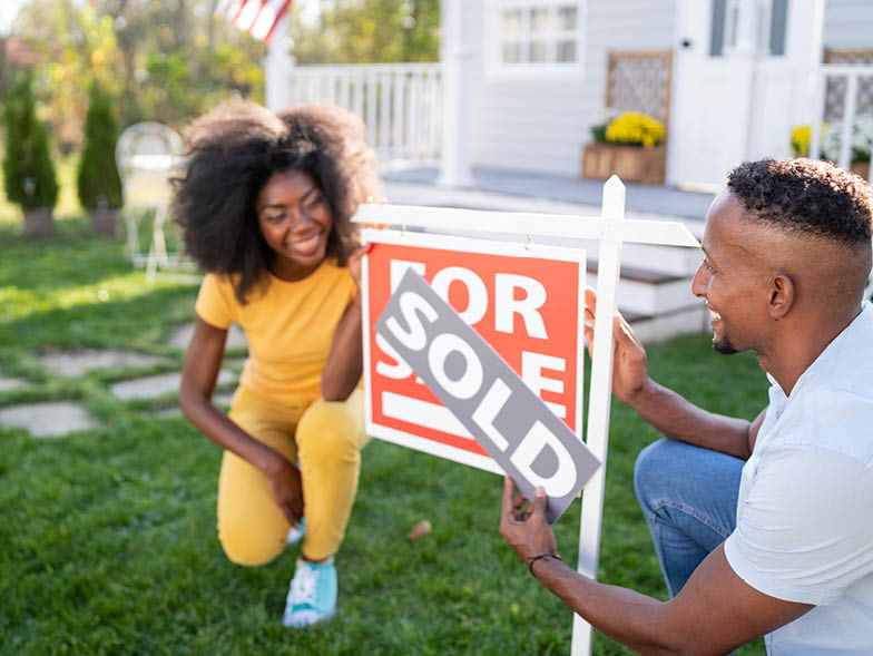 woman and man holding for sale sign