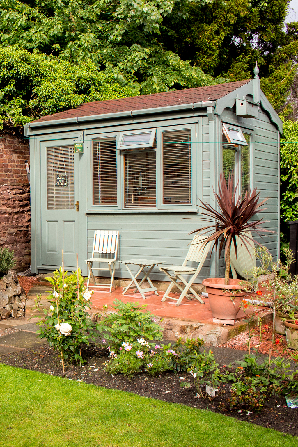 blue shed surrounded by landscaping