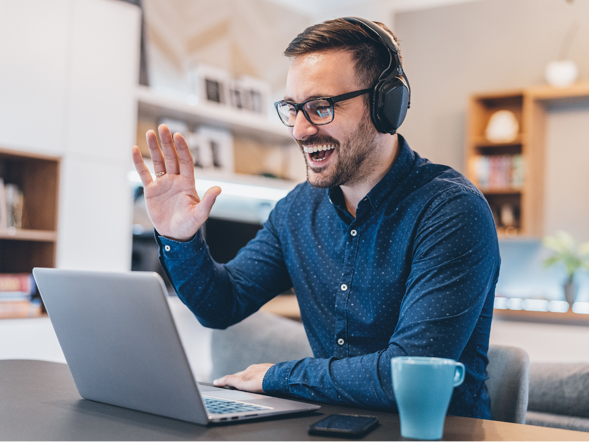 man with headphones waving on laptop