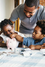 parent with children using a piggy bank